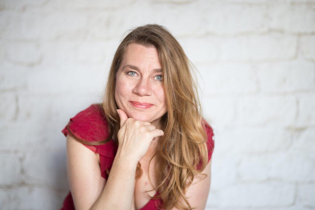 Chorleiterin Valérie Suty - mit langem blonden Haaren, sitzt in kurzärmeligen roten Kleid, lächelt, Kopf aufgestützt auf Hand.