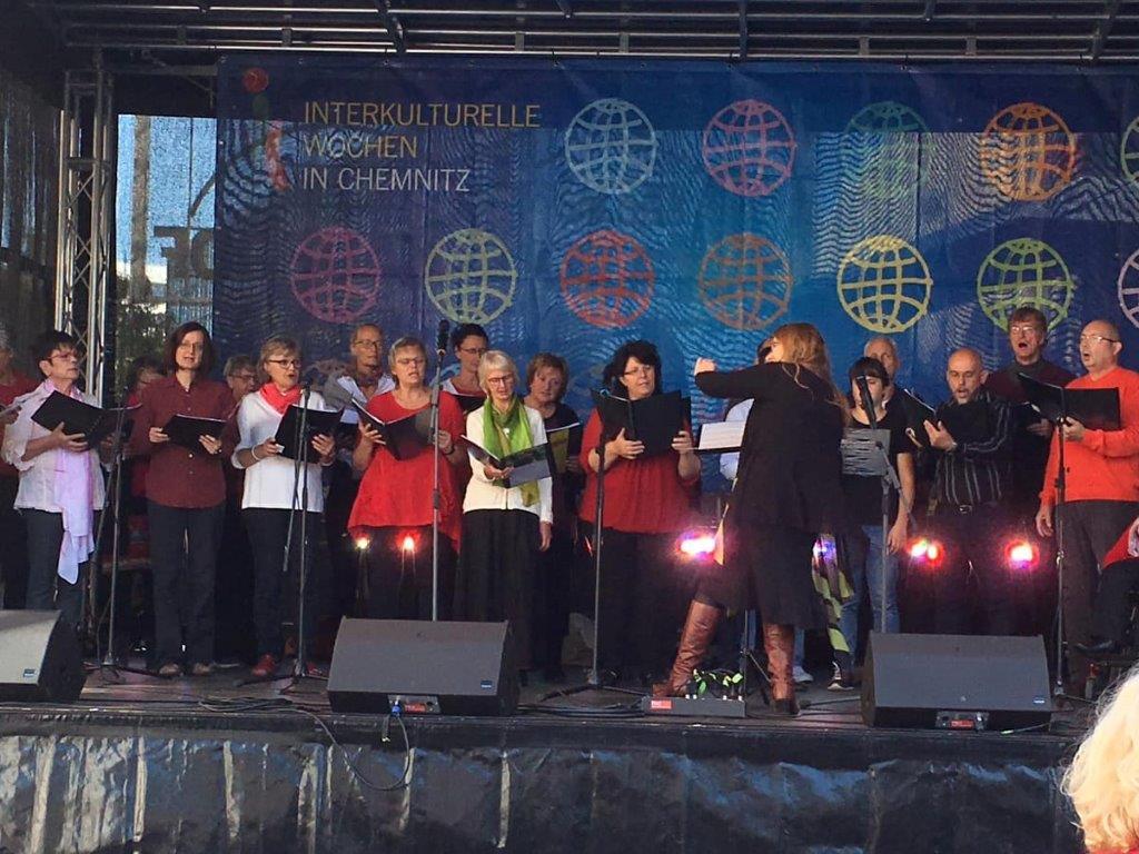 UNITY-Auftritt zu den Interkulturellen Wochen 2019 auf der Bühne auf dem Markt Chemnitz vor dem Rathaus. Chor steht bunt gekleidet auf der Bühne.