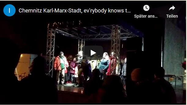 Chor UNITY steht vor dem Karl-Marx-Kopf auf kleiner Bühne. Es ist Abend, dunkel. Die Bühne ist beleuchtet. Link zum Youtube-Video Chemnitz Karl-Marx-Stadt.