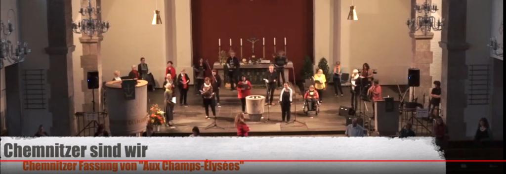 Foto: Chor UNITY steht im Altarbereich der Sankt-Pauli-Kreuzkirche und singt.