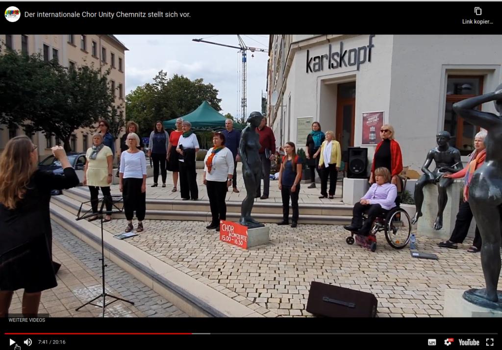 """Chor UNITY singt am Brühl. Die Chormitglieder stehen mit größerem Abstand an der Figurengruppe """"Urteil des Paris"""".  Link zum Youtube-Chorvideo: Der Chor stellt sich vor."""