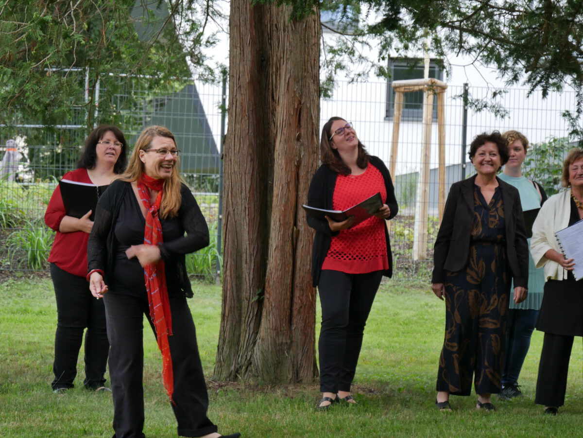 Die Chorleiterin und fünf Frauen des Chores lachen zum Publikum.