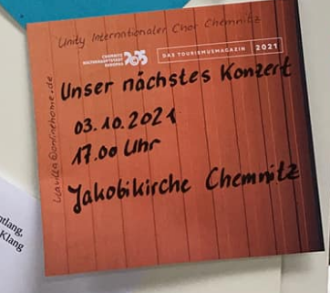 Auf einem braunen Zettel an der Pinnwand steht geschrieben: Unser nächstes Konzert 3.10.2021 17 Uhr Jakobikirche Chemnitz